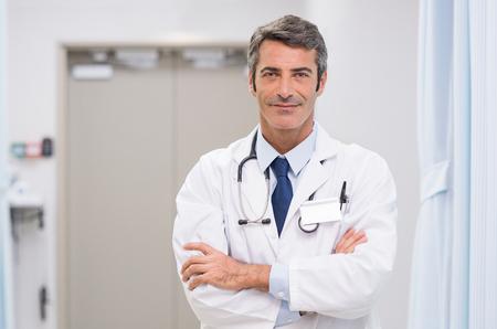 Retrato del doctor sonriente con el estetoscopio alrededor de su cuello en la clínica médica. Feliz sonriente médico senior en el vestíbulo del hospital. Hombre maduro que se siente confiado después de una operación importante y que mira la cámara.