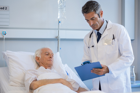 Mature doctor reading medical reports of a senior patient lying on bed at hospital. Doctor on a medical round while checking senior patients reports. Professional doctor with clipboard at hospital ward. Stock Photo