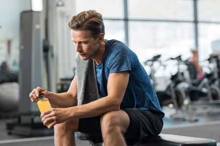 fruit: Young man in gym sitting alone opening a bottle of energy drink. Thoughtful fit man in gym holding fruit juice and thinking. Tired man in gym resting while drinking fruit juice.