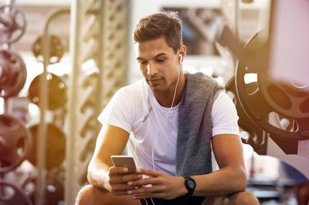 Hombre hermoso joven que usa el teléfono mientras que ejercicio se rompe en gimnasio. Chico musculoso con smartphone sentado en el banquillo después del entrenamiento diario. Hombre latino escuchando música mientras descansa después del ejercicio.