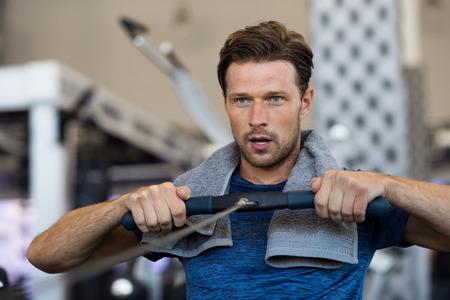 Fit man training op rij machine in de sportschool. Knappe man die uitoefent bij fitnessclub. Zweetige jonge man met een handdoek om nek die met roeimachine in de sportschool uitoefent.