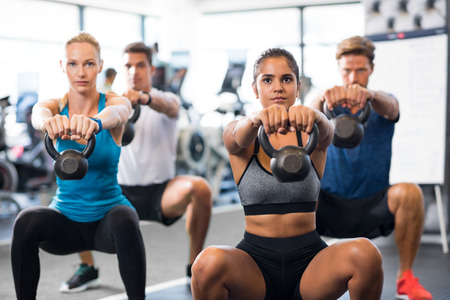 여자와 남자 체육관에서 kettlebells와 운동. 주전자 벨을 하 고 젊은 사람들의 그룹에는 쪼 그리고 앉는 함께 운동. 피트 니스 클래스와 여자 무게로 훈련