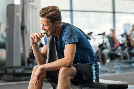 Sweaty joven comer barra de energía en el gimnasio. Apuesto chico mid disfrutando de chocolate después de un entrenamiento pesado en el estudio de fitness. Hombre apto mordiendo un refrigerio y descansando en el banco.