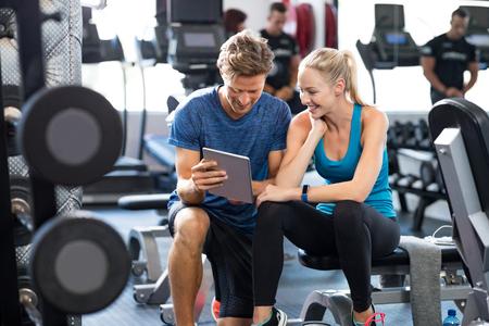 ジムで金髪の女性に話している間デジタル タブレットを使用してパーソナル トレーナーを笑っています。幸せなカップルは、フィットネス クラブ 写真素材