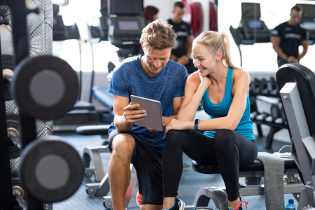 contemporary: Smiling personal trainer using digital tablet while talking to blonde woman at gym. Happy couple using tablet in fitness club. Client trainer looking at computer her progress at the gym.
