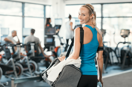 healthy body: Fit woman holding gym bag in a fitness centre. Beautiful blonde woman ready to start her training. Portrait of energetic woman looking at camera ready for new inscription at the gym.
