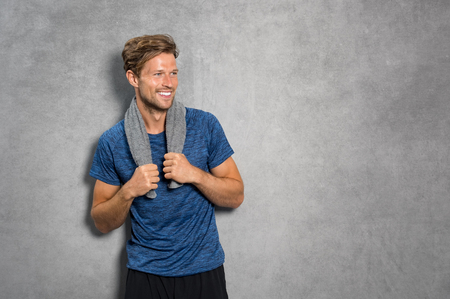 Portrait of a smiling fitness man with towel on shoulders looking away. Happy young man relaxing after training and leaning on grey wall. Sporty active guy resting after workout with copy space. Banque d'images