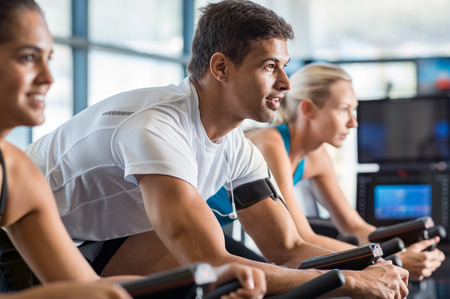Portrait of young man exercising using stationery bike in gym. Latin man biking in the gym with a group of people. Fitness class doing sport biking in the gym for fitness.