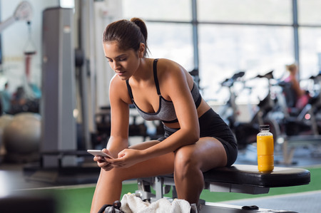 resting: Young woman athlete using cell phone at gym. Latin woman in sportswear checking phone while resting after workout on bench. Beautiful fit girl messaging with smartphone at fitness centre.