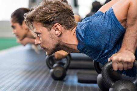 cross: Young man doing push up using kettlebells. Strong guy using kettlebells at gym during exercise. Determinated man doing push ups with kettle bell at the fitness centre. Stock Photo