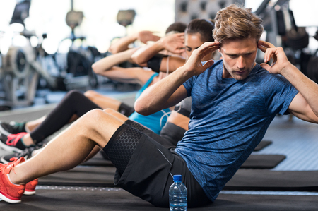 Muscular guy doing sit ups at gym with other people in background. Young athlete doing stomach workout in modern gym. Handsome fit man doing crunches at gym.