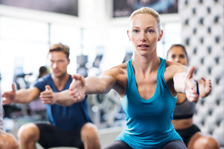 healthy body: Young woman exercising in gym with people in background. Fit woman exercising with stretched hands and squats in modern gym. Fitness class exercising in gym. Stock Photo