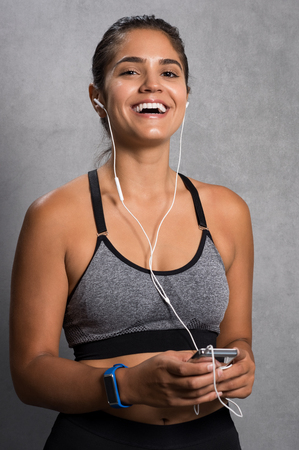real: Cheerful young woman having fun while listening to music. Fit girl holding mp3 player enjoying music after workout. Happy smiling athlete listening to music.