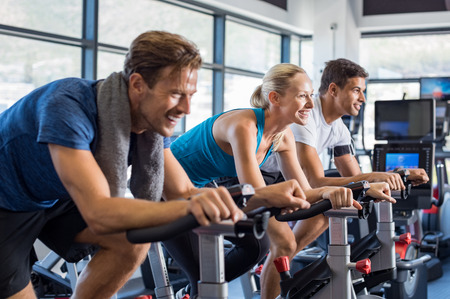 Group of smiling friends at gym exercising on stationary bike. Happy cheerful athletes training on exercise bike. Young men and woman working out at spinning class in the gym. Archivio Fotografico