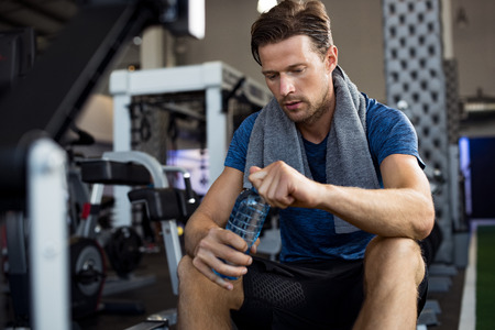 Young man with towel on his shoulders drinking water while sitting at gym. Sweaty guy opening cap of bottle to drink water after workout. Tired man resting after training and holding bottle of water. Banque d'images