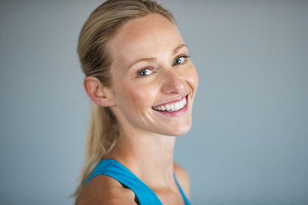 Portrait of a young woman smiling and looking at camera. Cheerful beautiful girl face feeling fresh over grey background. Close up face of carefree blonde woman laughing.