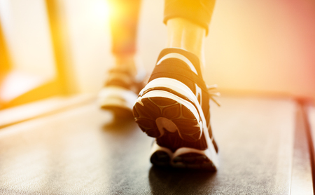 sport shoe: Fitness girl running on treadmill at gym. Rear view of detail of feet of young woman wearing sneakers and running on treadmill. Fitness and healthy lifestyle concept. Stock Photo