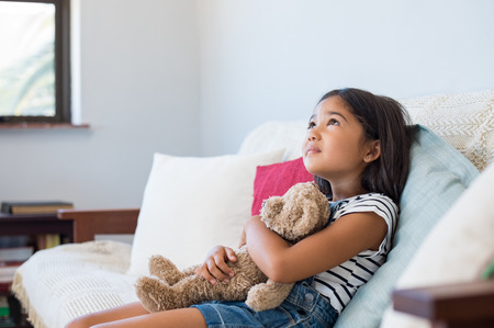 Young girl embracing teddy bear and  looking up. Pensive asian child hugging stuff toy on sofa. Thoughtful ethnic girl embracing her favorite toy and thinking about the future.