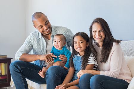 Retrato de la familia multiétnica feliz sentado en el sofá en casa. Sonriente pareja con los niños sentados en el sofá y mirando la cámara. Padre negro y mujer latina con la hija que se sienta en el sofá y que se divierte.
