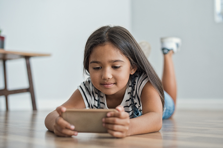 screen: Little asian girl lying on floor using mobile phone to play. Multiethnic female child watching cartoon on smartphone at home. Childhood and moder technology concept. Stock Photo