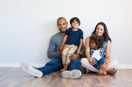 Familia multiétnica feliz sentada en el piso con los niños. Sonriente pareja sentada con dos hijos y mirando a cámara. Madre hispana y padre negro relajante con sus chicos lindos apoyándose en la pared con espacio de copia.