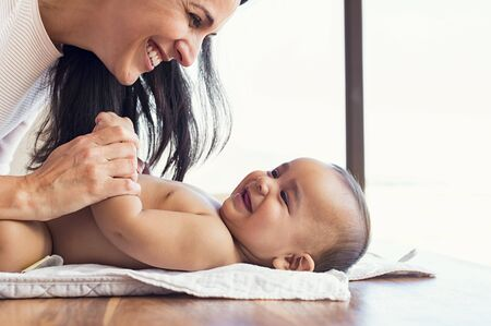 woman in bath: Happy mother playing with baby while changing his diaper. Smiling young woman with baby son on changing table at home. Close up of cheerful mom and toddler boy playing together. Stock Photo