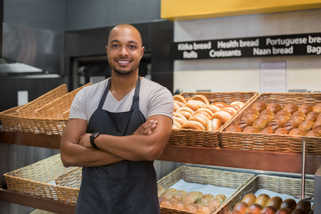 work: Smiling baker man standing with fresh bread at bakery. Happy african man standing with crossed arms at counter in bake shop and looking at camera. Satisfied baker with breads in background.
