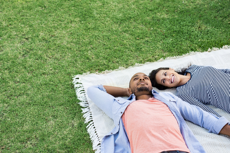 Young multiethnic couple lying on blanket on grass. Latin woman with her african boyfriend relaxing on picnic blanket outdoor. Mature happy couple in love lying on grass with copy space. Фото со стока