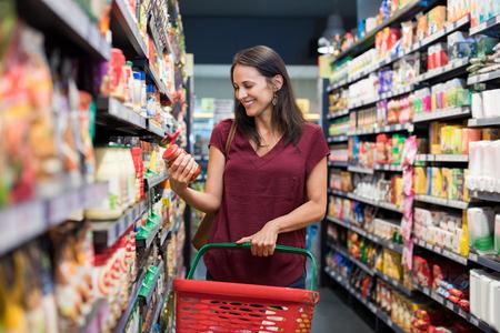 Gelukkige rijpe vrouw kijken naar het product in de supermarkt. Glimlachende Spaanse vrouw winkelen in supermarkt en lezen van productinformatie. Koper die voedsel op de markt koopt.