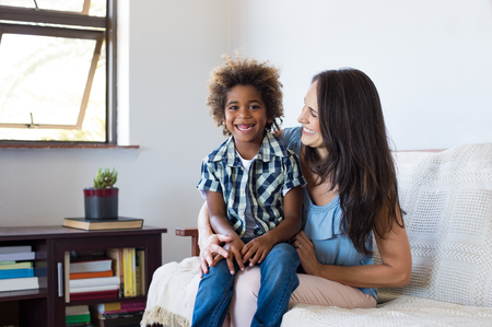 family sofa: Happy latin mother embracing her adopted son on couch and smiling. Cheerful woman playing with her african child at home. Portrait of son and mom having fun together after school. Stock Photo