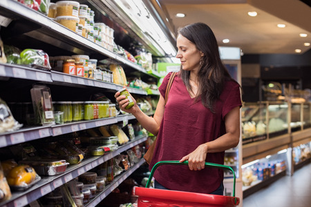 store shelf: Young woman shopping in grocery store. Mature woman checking food label in supermarket. Latin woman holding shopping basket and choose a product in supermarket.