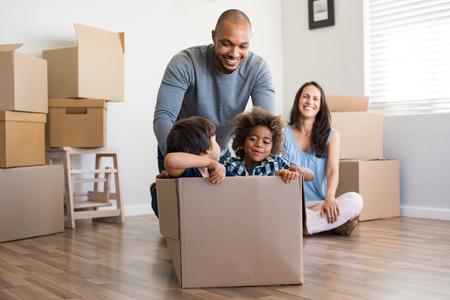 Feliz padre afroamericano jugando con los niños sentados en caja de cartón en el nuevo hogar. Feliz familia multiethinc disfrutando de nuevo hogar. Jóvenes padres e hijos se divierten durante la mudanza. Foto de archivo