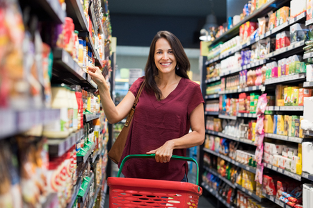 store shelf: Happy mature woman looking at camera while shopping in grocery store. Casual woman choosing food from shelf in supermarket and looking at camera. Smiling customer standing near shelves. Stock Photo