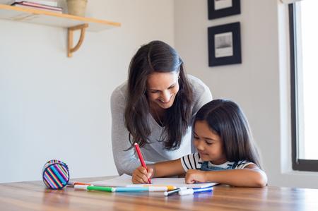 Gelukkige moeder en lachende dochter samen schilderen met markers. Moeder helpt geadopteerd kind met kunst huiswerk. Vrolijke moeder en Aziatisch meisje schilderen thuis.