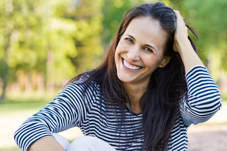 real: Happy latin woman having fun at park while touching hair. Hispanic woman enjoying holiday while sitting on grass in park. Portrait of smiling mature woman relaxing and looking at camera.