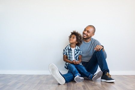 African father and his son sitting on floor and looking up in a blank wall. Happy dad and little boy sitting in an empty room. Young black man with his child thinking and pensive with copy space. Archivio Fotografico