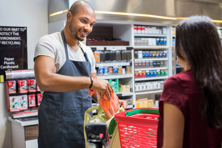 supermarket: Smiling salesman putting vegetables in bag for customer after billing. Cashier black man at grocery store helping customer pack purchased products. Happy young man working in grocery shop.