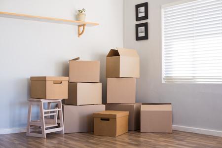 Pile de boîtes en carton dans une pièce vide. Pile de boîtes en carton au sol dans un appartement vide. Pièce de boîtes en mouvement dans une nouvelle maison. Banque d'images