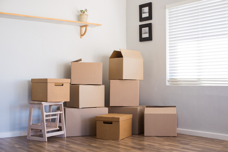 Stack of cardboard boxes in an empty room. Pile of carton boxes on the floor in an empty apartment. Stack of moving boxes in new house. Stockfoto