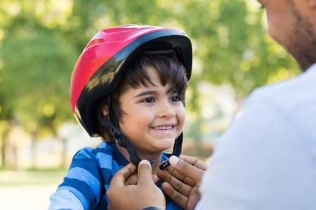 サイクル ヘルメット身に着けている陽気な息子を助けての父。サイクリングを開始する準備をしてバイクのヘルメットを着用して少年を興奮させた