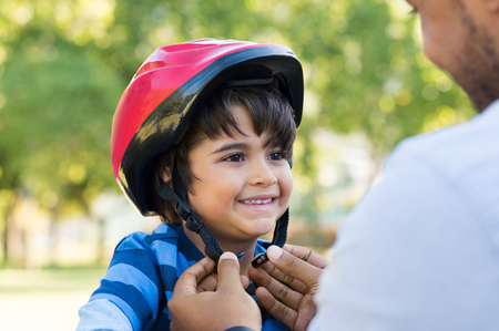 Father helping cheerful son wearing helmet for cycle. Excited little boy getting ready by wearing bike helmet to start cycling. Happy cute boy learn to ride a bike with his dad. Banco de Imagens - 80342714