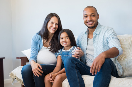 african american woman: Happy multiethnic couple with their daughter sitting couch at home. Smiling family with one child expecting another baby. Pregnant mother sitting with daughter and black husband on couch.