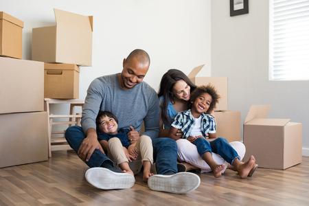 Gelukkige familie met twee kinderen die plezier hebben in een nieuw huis. Jonge multietnische ouders met twee zonen in hun nieuwe huis met kartonnen dozen. Lachende kleine jongens zitten op de vloer met moeder en vader. Stockfoto