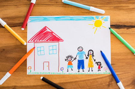 table top: Top view of colored drawing of happy family holding hands together. Little child painted his family on paper with colorful marker. High angle view of painting and markers on table. Concept of unity and love.