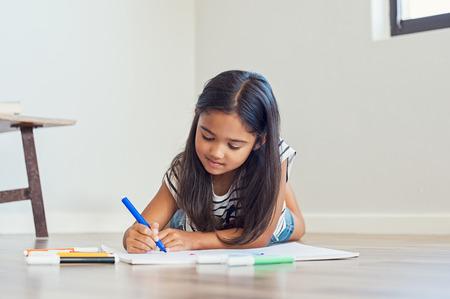 Weinig Aziatisch meisje die bij vloer het schilderen met gekleurde teller liggen. Leuk Indisch meisje die op de vloertekening liggen in de woonkamer thuis. Mooie multi-etnische kindtekening.