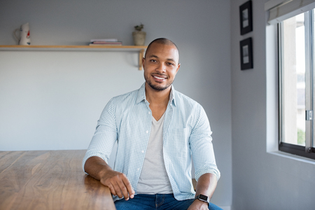 1 person: Smiling young african american man sitting on table at home. Portrait of black guy in casual looking at camera indoor. Carefree happy man relaxing at home.