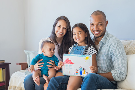 Daughter showing drawing of a happy family outside a new house. Cute infant looking at colorful drawing of his sister. Happy proud multiethnic parents sitting with children on sofa  and looking at camera.