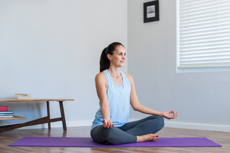 asana: Mid adult woman sitting in lotus position on purple mat at home. Young serene woman feeling relaxed while meditating at home. Happy woman doing yoga and looking away.