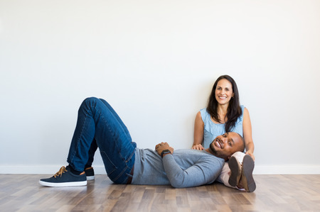 Young multiethnic couple relaxing on floor and looking at camera with copy space. Happy african man resting on the leg of his girlfriend after move house. Black guy lying on ground with her wife in new home.