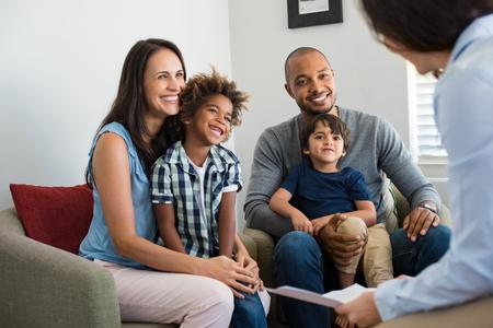 Glückliche junge Familie sitzt auf Couch und spricht mit Familienberater. Lächelnde Eltern mit adoptierten Kindern diskutieren mit Berater. Multiethnische Familie, die einen Finanzagenten trifft.
